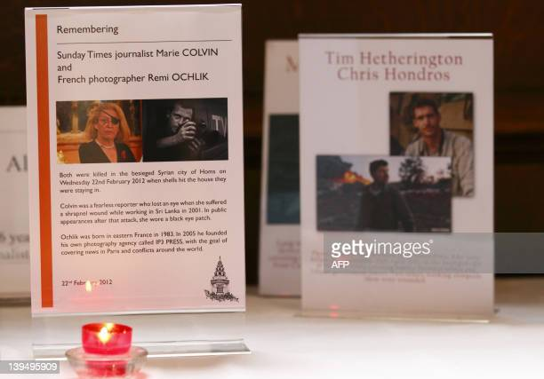 A candle burns in front of a memorial plaque remembering USborn Sunday Times journalist Marie Colvin and French photographer Remi Ochlik who were...