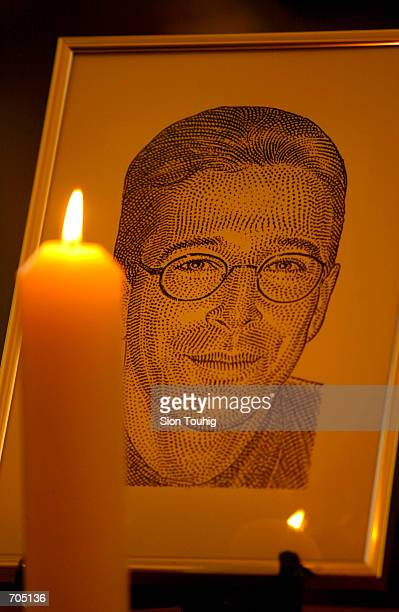 Candle flickers next to a portrait of Wall Street Journal reporter Daniel Pearl March 5, 2002 at a memorial service in St Brides Church in London....