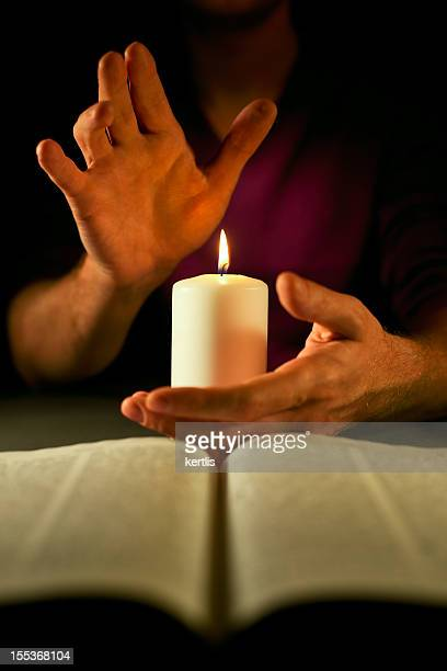 Candle, hands and bible