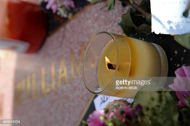 A candle lit at a makeshift memorial to actor/comedian Robin Williams at his star on the Hollywood Walk of Fame August 12 in Hollywood California...