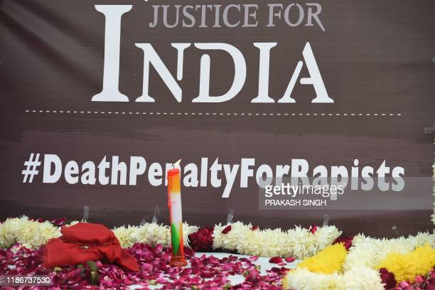 Candle lit by demonstrators is seen during a protest against the alleged rape and murder of a 27-year-old veterinary doctor in Hyderabad, during a...