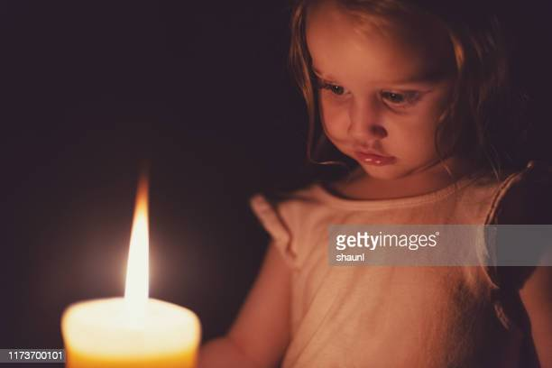 candle lit girl - blackout picture stock pictures, royalty-free photos & images