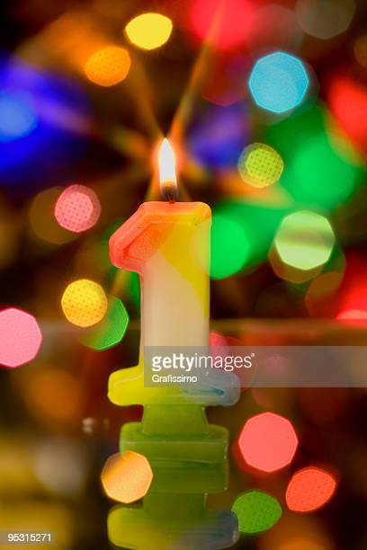 Candle number one on colorful background