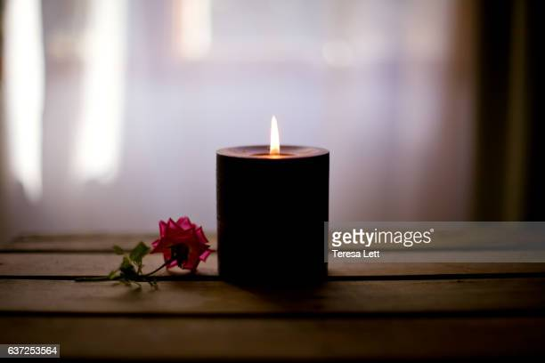 candle on a table with a rose - candlelight stock pictures, royalty-free photos & images