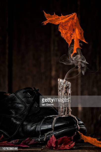 candle on shoe_1 - ian gwinn stock photos and pictures