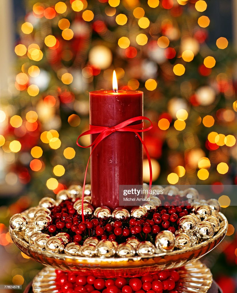Candle placed in the center of some sweets arranged in a bowl : Stock Photo
