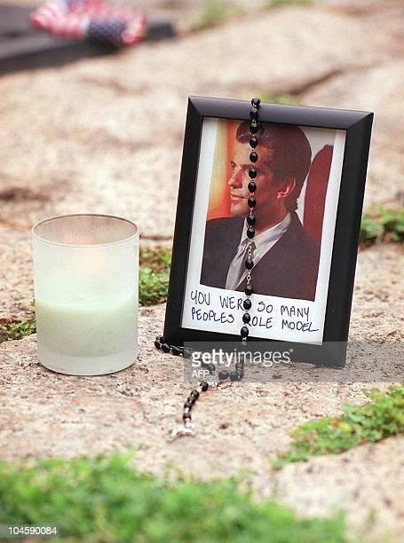 A candle rosary beads and a photo of John F Kennedy Jr adorn the gravesite of his father assassinated US President John F Kennedy 21 July 1999 at...