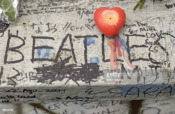 A candle sits on a graffitiridden wall outside the Abbey Road Studios for former Beatles singer and guitarist George Harrison November 30 2001 in...