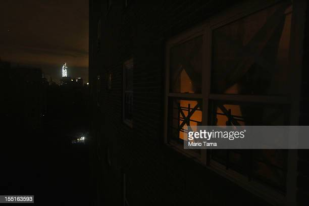 Candlelight glows through the window of an apartment without power in the Jacob Riis housing projects in Manhattan's East Village in front of the...