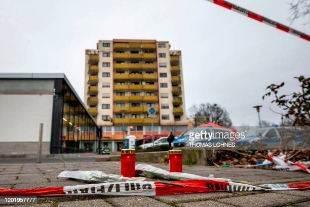 Candles amd flowers lay behind a police cordon in front of one of the bar target in a shooting in Kesselstadt near Frankfurt western Germany on...