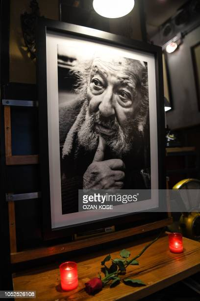 Candles and a rose have been put next to a portrait of late Turkish photographer Ara Guler on October 19, 2018 at Ara Cafe in Istanbul. - Legendary...