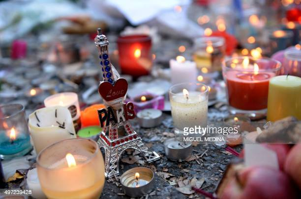 Candles and a small statue of the Eiffel Tower are placed at a memorial along a police cordon setup close to the Bataclan concert hall on November 15...