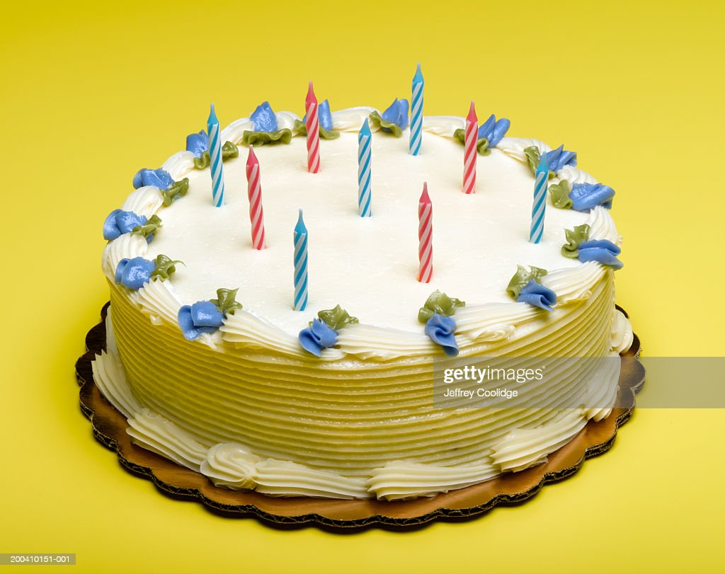 Candles And Blue Decorative Flowers On Birthday Cake Stock Photo