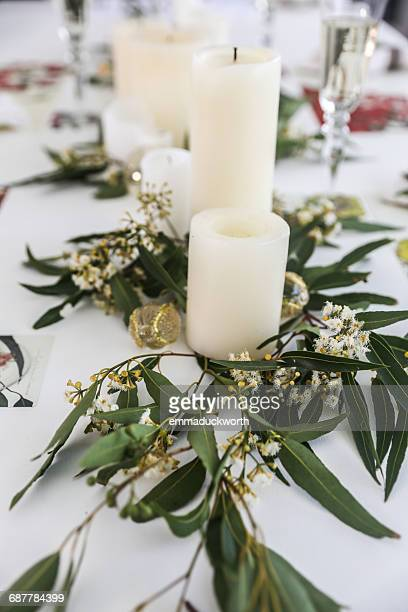 Candles and eucalyptus centerpiece on dining table