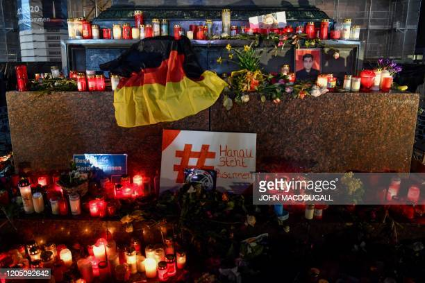 Candles and flowers are left at a memorial for the victims of a gunman who killed nine people in a racist attack at the market square in Hanau,...