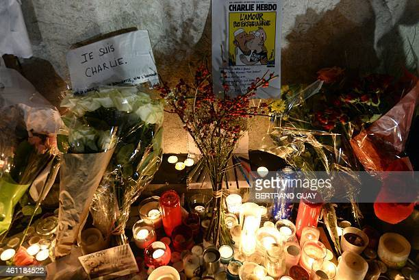 Candles and flowers are placed around a poster of one of Charlie Hebdo's covers next to a sign reading 'I am Charlie' during a rally at Republic...