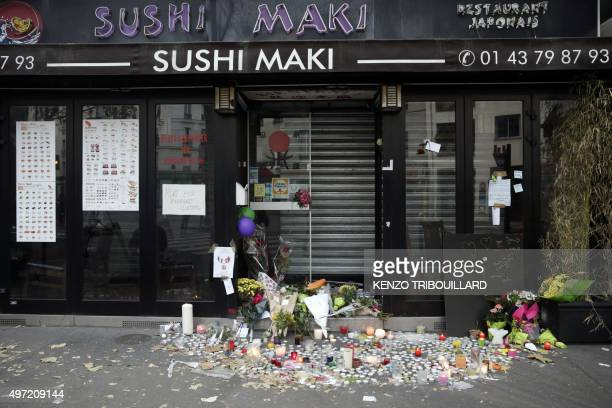 Candles and flowers are placed at the entrance of Japanese restaurant next to the cafe 'La Belle Equipe', Rue de Charonne, on November 15, 2015 in...
