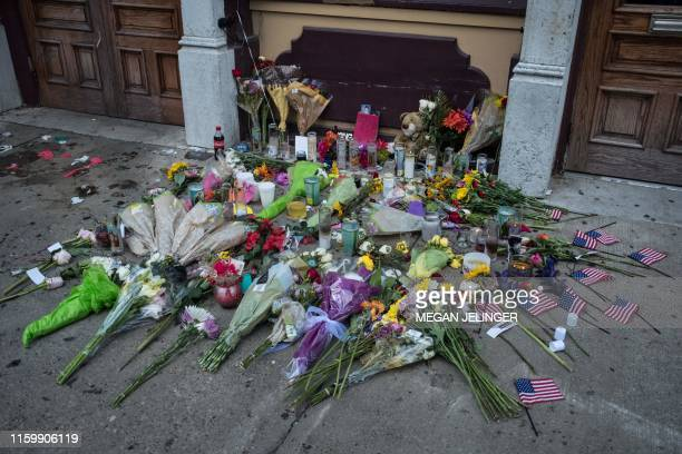 Candles and flowers are placed outside of Ned Peppers after the mass shooting over the weeeknd outside of the bar in Dayton Ohio on August 5 2019 US...