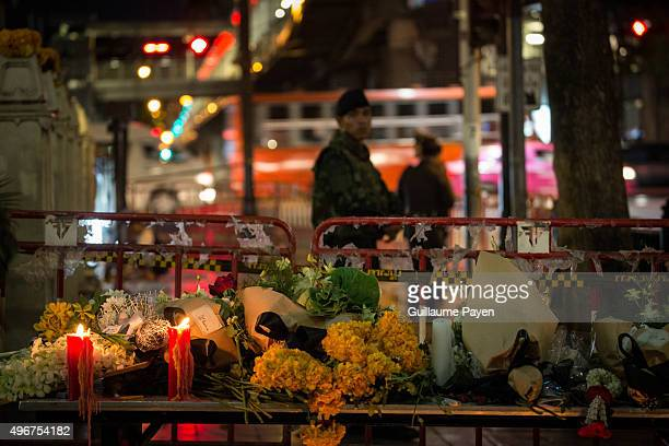 Candles and flowers can be seen outside the Erawan Shrine, 24 hours after the deadly blast at the Ratchaprasong intersection in Bangkok, Thailand, on...