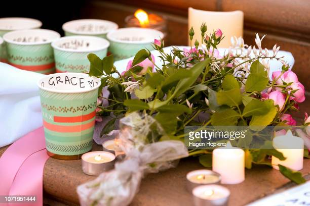 Candles and flowers from members of the public surround a photo of British backpacker Grace Millane during a vigil at Civic Square on December 12...