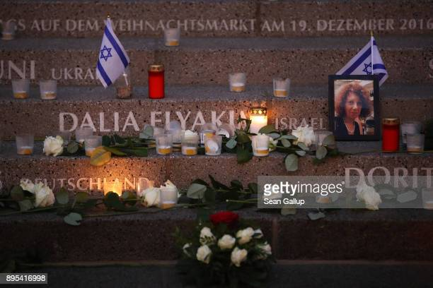 Candles and flowers lie at the inscription to Israeli victim Dalia Elyakim and other victims at a memorial shortly after the memorial's inauguration...