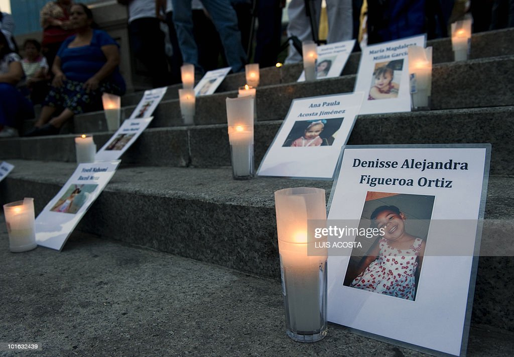 Candles and images of a day care fire victims are display on the floor at the Independence Angel Monument during a protest in Mexico City, June 4, 2010. Relatives of 49 children killed in a day care fire a year ago in Hermosillo, Mexico, demanded the officials, who failed to ensure the center's safety, be brought to justice. AFP PHOTO/Luis Acosta