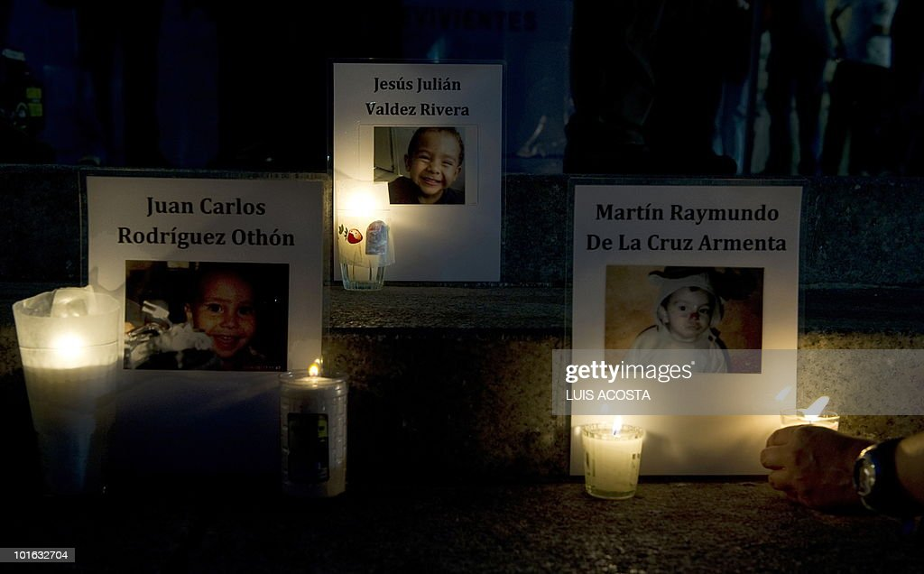 Candles and images of a day care fire victims are display on the floor at the Independence Angel Monument during a protest in Mexico City, June 4, 2010. Relatives of 49 children killed in a day care fire a year ago in Hermosillo, Mexico, demanded the officials, who failed to ensure the center's safety, be brought to justice.AFP PHOTO/Luis Acosta