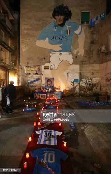 Candles and jerseys are pictured at a makeshift altar set up in the Quartieri Spagnoli of Naples on November 26, 2020 to mourn the death of...