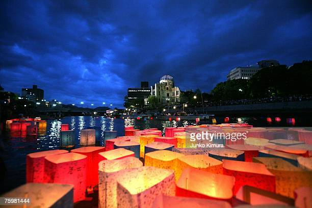 Candles and paper lanterns float on the Motoyasu River in front of the Atomic Bomb Dome at the Peace Memorial Park in memory of the victims of the...