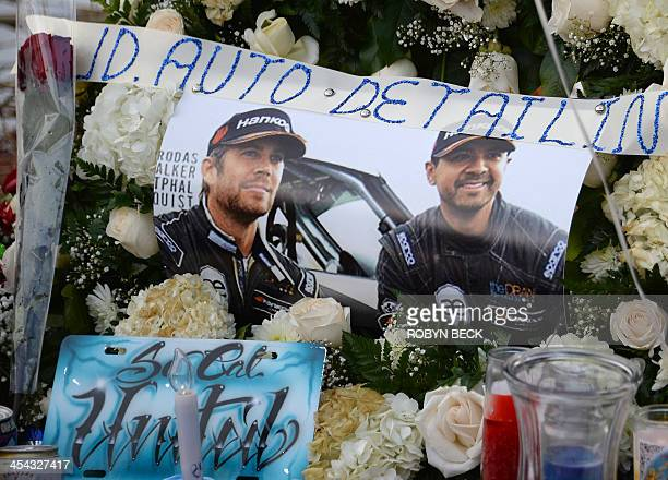 """Candles and pictures are seen among other mementos left by fans of actor Paul Walker at a memorial rally and car cruise to remember the """"Fast and..."""