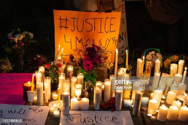 Candles and signs are seen during a vigil for Manuel Ellis a black man whose March death while in Tacoma Police custody was recently found to be a...