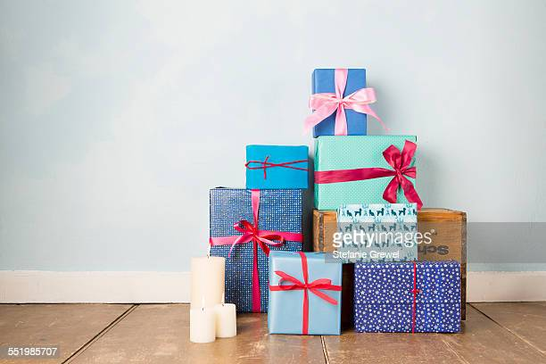 candles and stack of wrapped christmas gifts on wooden floor - caja de regalo fotografías e imágenes de stock