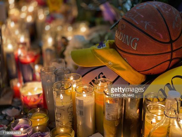 Candles are displayed at a makeshift memorial in front of a mural for former NBA and Los Angeles Lakers player Kobe Bryant in downtown Los Angeles on...