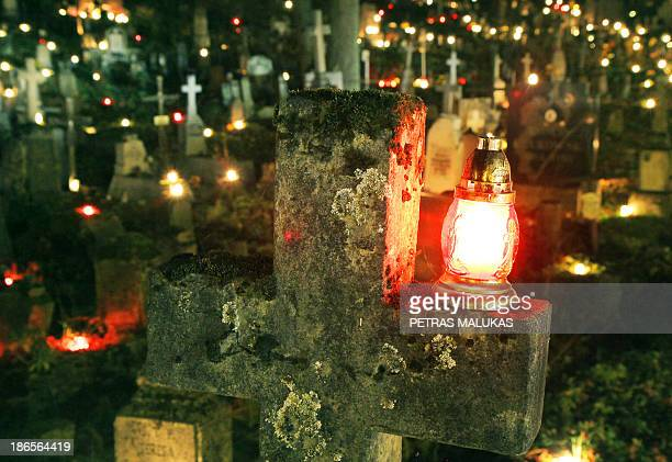Candles are lighted on tombs on the occasion of All Saints' Day on the Rasos cemetery in Vilnius Lithuania on November 1 2013 In Lithuania people...