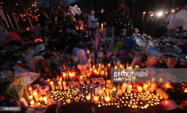 Candles are lit among mementos at a memorial for victims of the mass shooting at Sandy Hook Elementary School on December 17 2012 in Newtown...