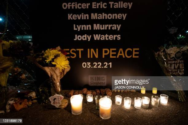 Candles are lit on March 23, 2021 under a sign listing the names of some of those killed in a mass shooting at a King Soopers grocery store in...