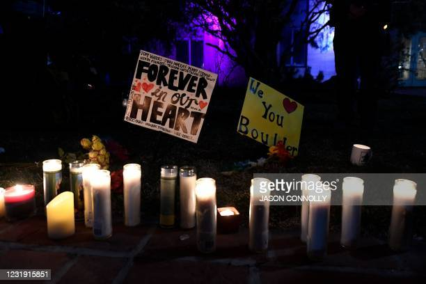 Candles are lit under signs during a candlelight vigil at the Boulder Courthouse in Boulder, Colorado on March 24 to honor the ten people killed...