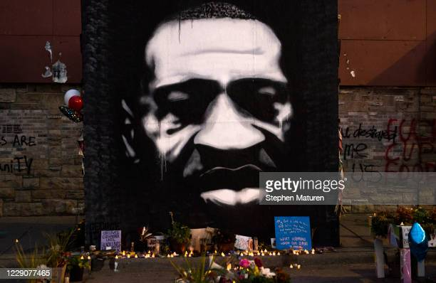 """Candles are placed beneath a portrait of George Floyd during a birthday celebration for him at a memorial site known as """"George Floyd Square"""" on..."""