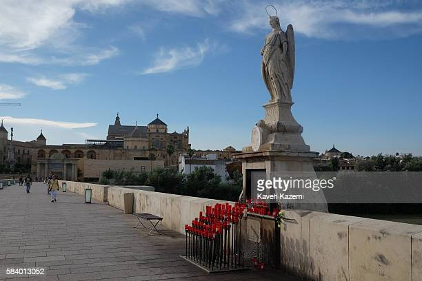 Candles are placed in front of Saint Raphael's shrine on Roman Bridge built over Guadalquivir river on June 26 2016 in Cordoba Spain The statue of...
