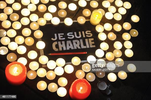 Candles are placed next to a sign reading 'Je suis Charlie' and a pen in La Rochelle on January 7 as people gathered to pay tribute to the twelve...