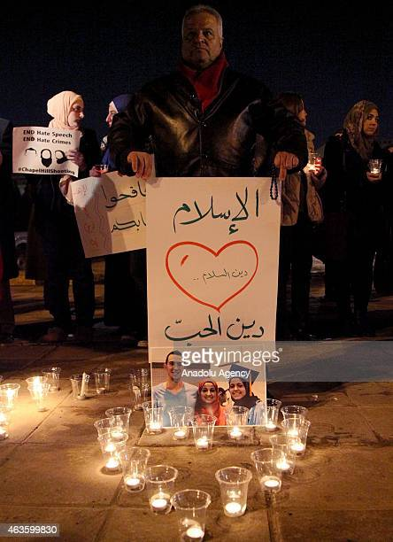 Candles are seen as a group of demonstrators gather in front of American Embassy in Amman to protest against the Chapel Hill shooting in Amman Jordan...