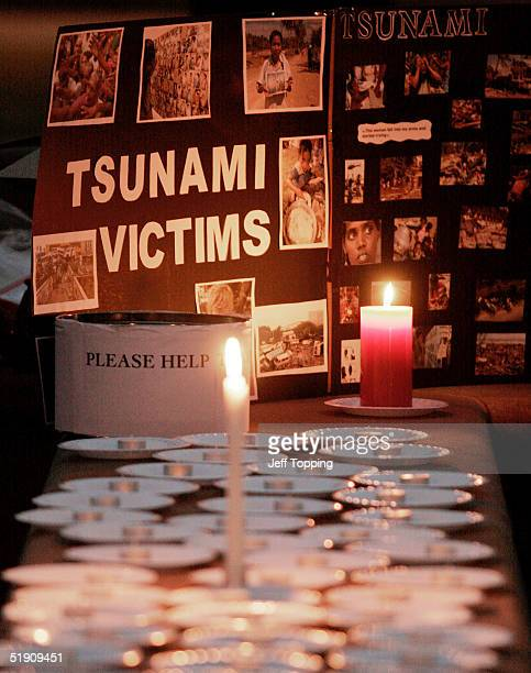 Candles burn at a display with photos of victims of the Southeast Asian tsunami during a vigil on the campus of Arizona State University sponsored by...
