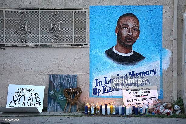 Candles burn at a memorial for Ezell Ford in Los Angeles as protestors demonstrate as people gather to protest after two grand juries decided not to...