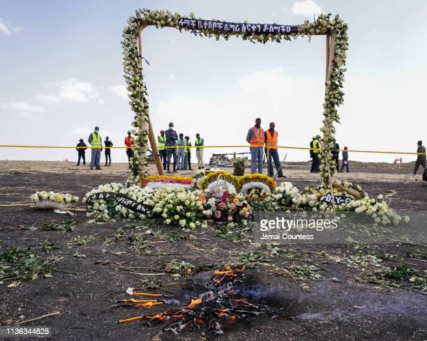 Candles burn before a flower adorned memorial arch erected at the site of the Ethiopian Airlines Flight ET302 crash on March 14 2019 in Ejere...