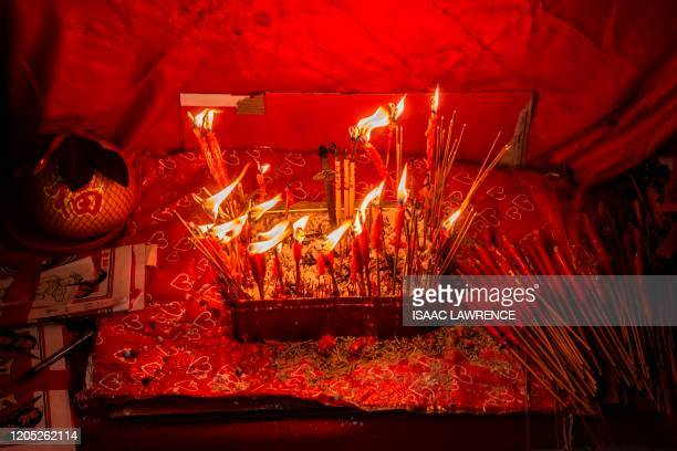 "Candles burn on a shrine used in a ""villain hitting"" ritual in the Causeway Bay district of Hong Kong on March 5, 2020. - Villian hitting or petty..."