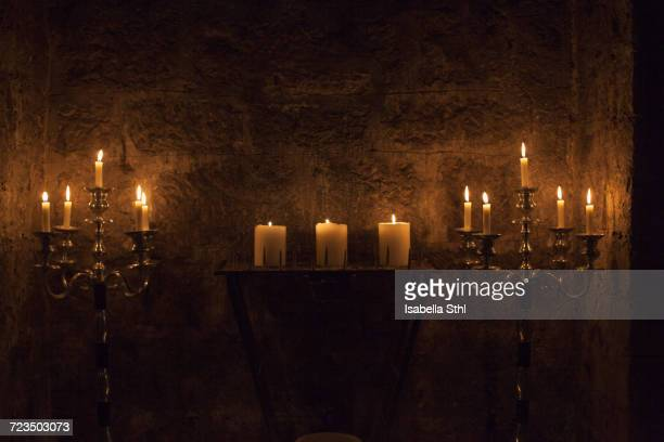 candles burning against stone wall - isabella stone stock photos and pictures