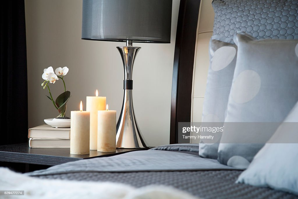 Candles burning beside a bed : Stock Photo