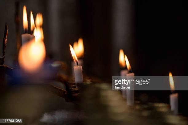 candles burning in a catholic church - religious vigil stock pictures, royalty-free photos & images