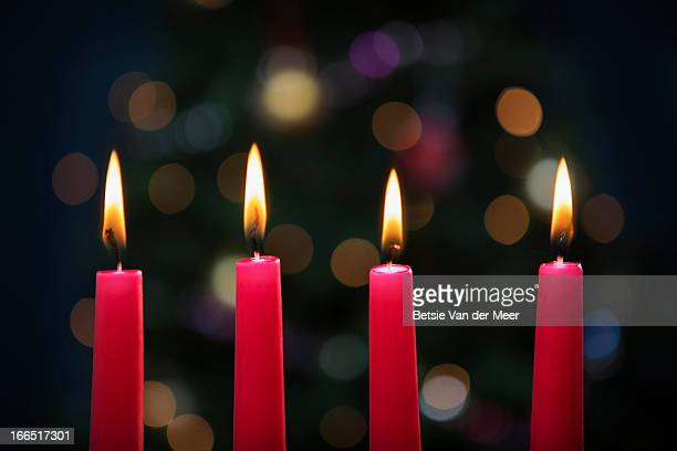 Candles burning in front of Christmas tree.