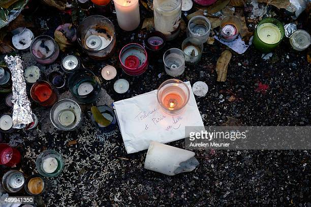 Candles can be seen in front of the Bataclan as people continue to leave tributes to victims at attack sites in Paris on December 4 2015 in Paris...